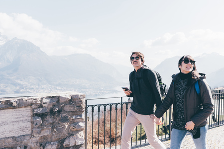 anorak: Couple strolling above lakeside,Monte San Primo,Italy