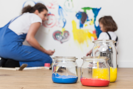 dungarees: Mother and daughter drawing on white wall