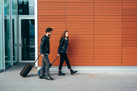 Couple with luggage,orange wall background,Florence,Italy