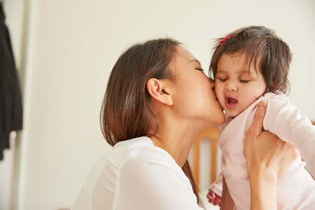 Woman kissing tired baby daughter in bedroom