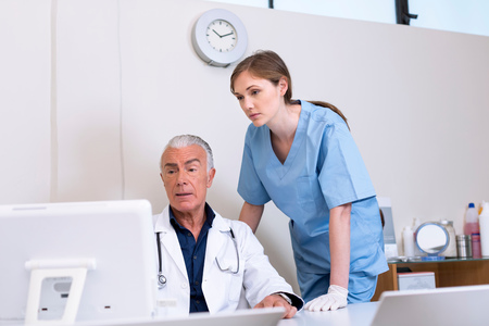 conferring: Doctors looking at computer