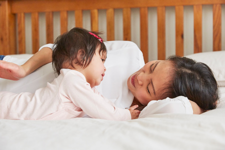 Woman reclining on bed with baby daughter LANG_EVOIMAGES