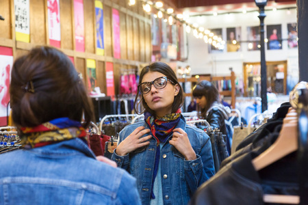 mirror image: Over shoulder mirror image of young female shopper trying on scarf in market hall LANG_EVOIMAGES