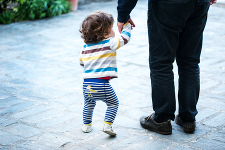 Father walking with young son,holding hands,rear view,low section LANG_EVOIMAGES