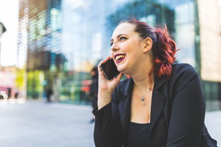 Young red haired businesswoman making smartphone call outside office