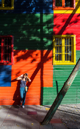 Woman leaning against colourful house,La Boca,Buenos Aires,Argentina