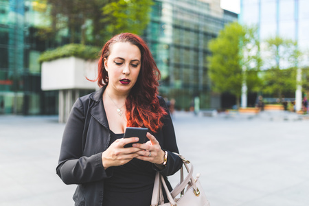 Young red haired businesswoman looking at smartphone outside office
