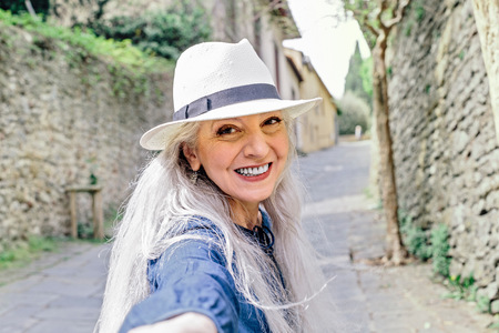 Portrait of stylish mature woman on cobbled street,Fiesole,Tuscany,Italy