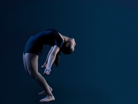 Low key shot of young female dancer standing and bending over backwards