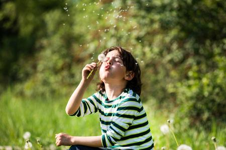 Young boy,sitting in field,blowing on dandelion clock