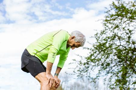 tiredness: Exhausted senior man,bending over,hands on knees