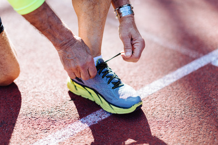 Cropped view of man on racetrack tying shoelace