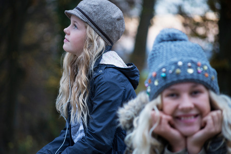 anorak: Portrait of girl and her sister in rural landscape wearing knit hat