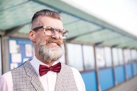 vintage: Portrait of stylish senior man with eyeglasses and handlebar moustache  on pier LANG_EVOIMAGES