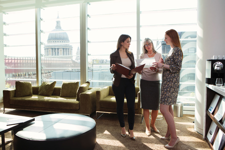 conferring: Businesswomen meeting by office sofa,London,UK LANG_EVOIMAGES