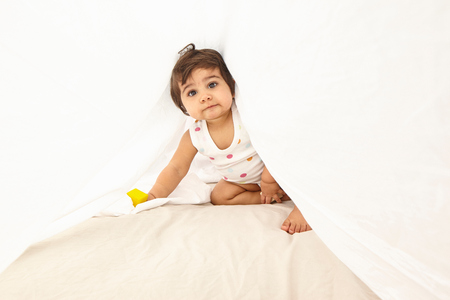 Portrait of toddler,crawling between sheets