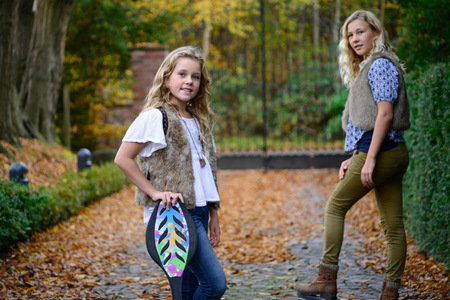 Portrait of two sisters with long blond hair in autumn park LANG_EVOIMAGES