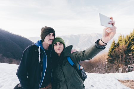 anorak: Hiking couple taking selfie in snowy mountains,Monte San Primo,Italy LANG_EVOIMAGES