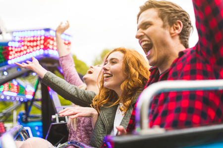 Group of friends on fairground ride,arms raised,laughing LANG_EVOIMAGES