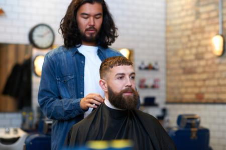 Hairdresser in barbershop putting protective cape on customer LANG_EVOIMAGES