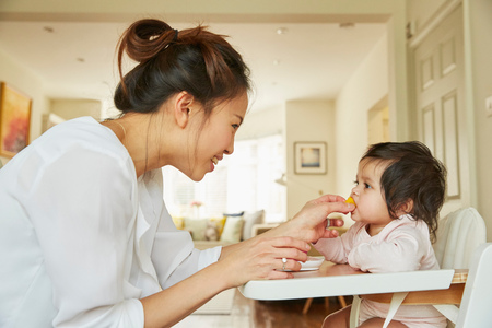 Woman feeding baby daughter in high chair