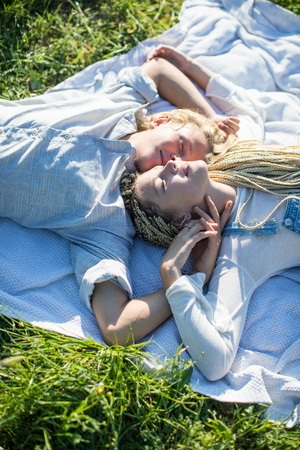 Overhead view of romantic young couple lying on picnic blanket in grass,Majorca,Spain