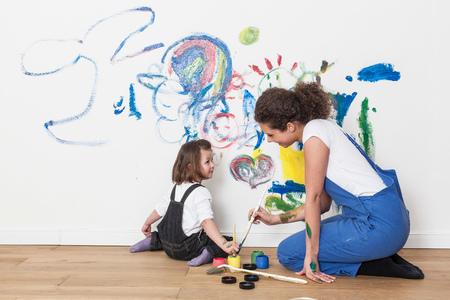 arrodillarse: Madre e hija dibujando en la pared blanca