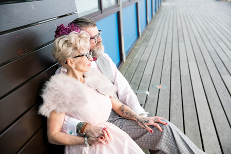 1950s vintage style couple sitting on pier bench