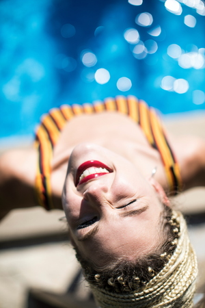 Young woman with dreadlocks,beside swimming pool,elevated view