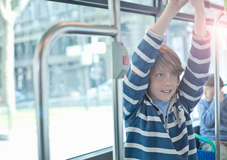 Boy holding handrail on bus