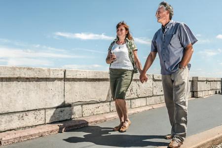 65 69 years: Older couple holding hands on bridge