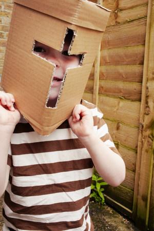 Boy wearing cardboard helmet outdoors LANG_EVOIMAGES