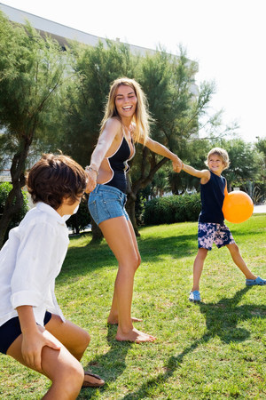 Kids pulling young womans hand on lawn
