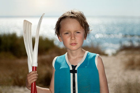 Boy holding rows on beach LANG_EVOIMAGES