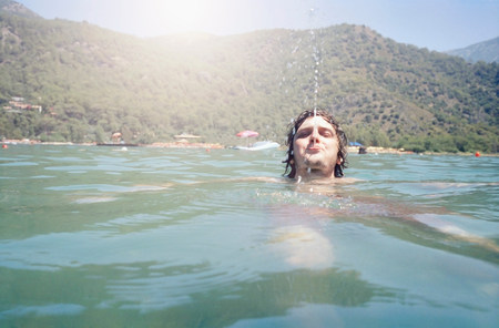 rudeness: Man swimming and blowing water from mouth