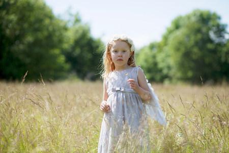 Girl wearing angel wings in field LANG_EVOIMAGES