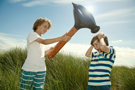 Boys playing with toy hammer outdoors LANG_EVOIMAGES