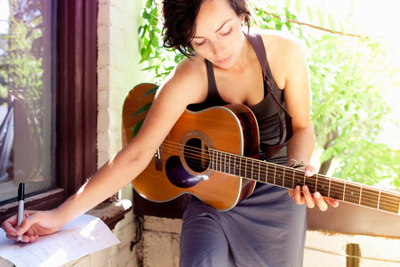Woman writing music with guitar