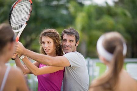Tenisový trenér demonstruje se studenty LANG_EVOIMAGES