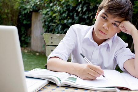 Boy doing homework in garden