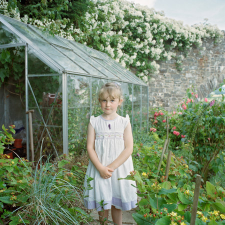 scottish female: Little girl standing by greenhouse LANG_EVOIMAGES