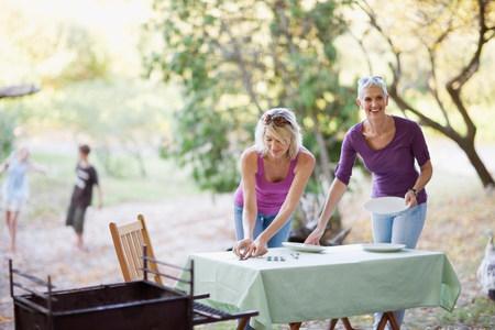 Ženy nastavení stolů venku LANG_EVOIMAGES