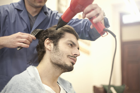 Barber drying customers hair with hairdryer