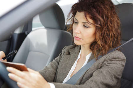 drivers seat: Businesswoman in car with notebook and pen