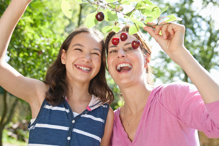 Mother and daughter picking fruit