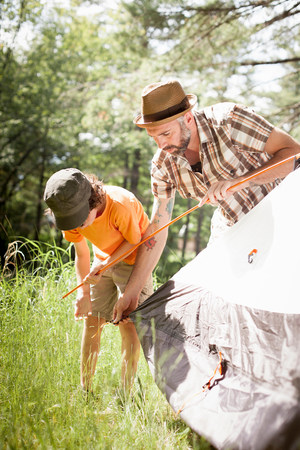getting out: Father and son pitching tent in forest LANG_EVOIMAGES