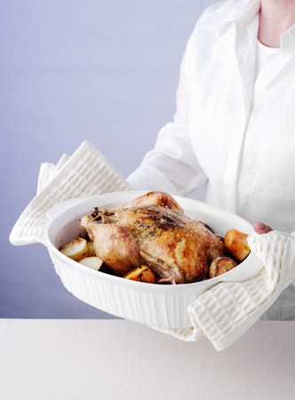 sultry: Woman holding dish of roast chicken