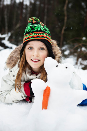 Smiling girl playing with snowman LANG_EVOIMAGES