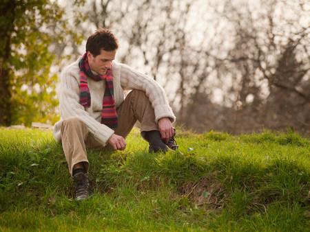 tiredness: Man sitting in grassy field LANG_EVOIMAGES