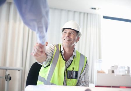 sinergia: Empresarios estrechándole la mano en el escritorio